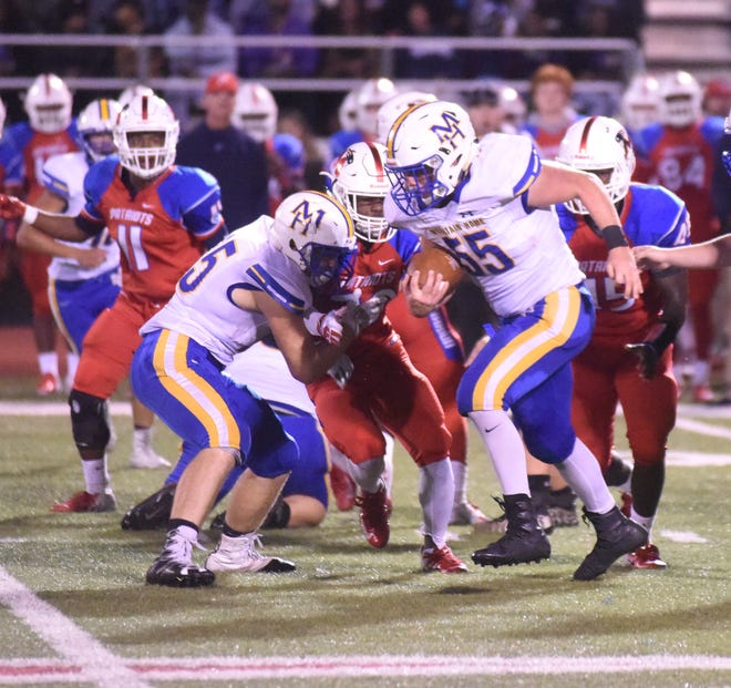 Mountain Home's Trace Rick (55) runs for a 64-yard gain while getting a block from Gage Hershberger on Friday at Marion.