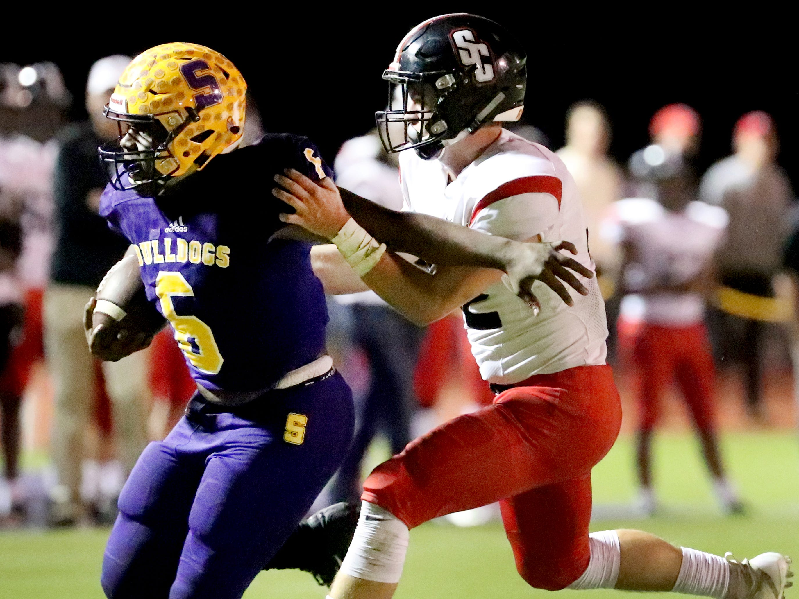 Smyrna's Mike Hartfield (6) runs the football as Stewarts Creek's Sam Slaughter (32) makes a tackle at Smyrna High School on Friday, Oct. 12, 2018.