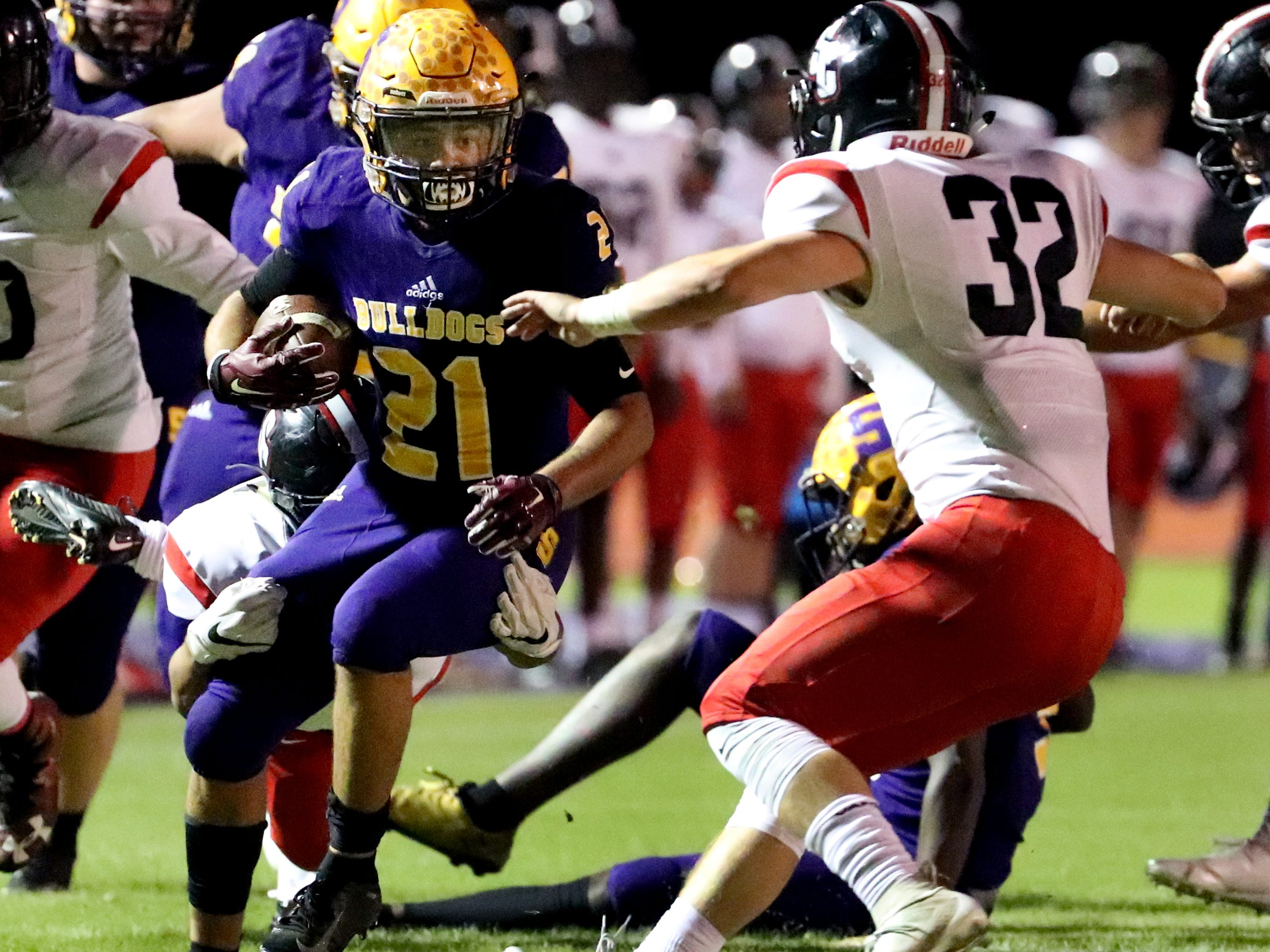 Smyrna's Blake Watkins (21) runs the football as Stewarts Creek's Sam Slaughter (32) moves in for a tackle at Smyrna High School on Friday, Oct. 12, 2018.