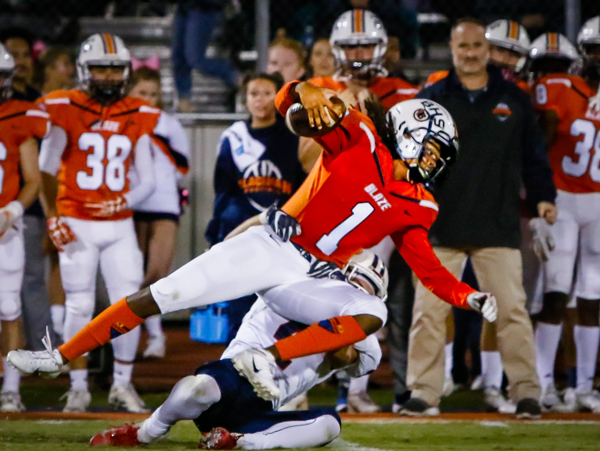 Blackman's Adonis Otey fights for more yardage while being taken to the ground by Cookeville's Jacob Stamps.