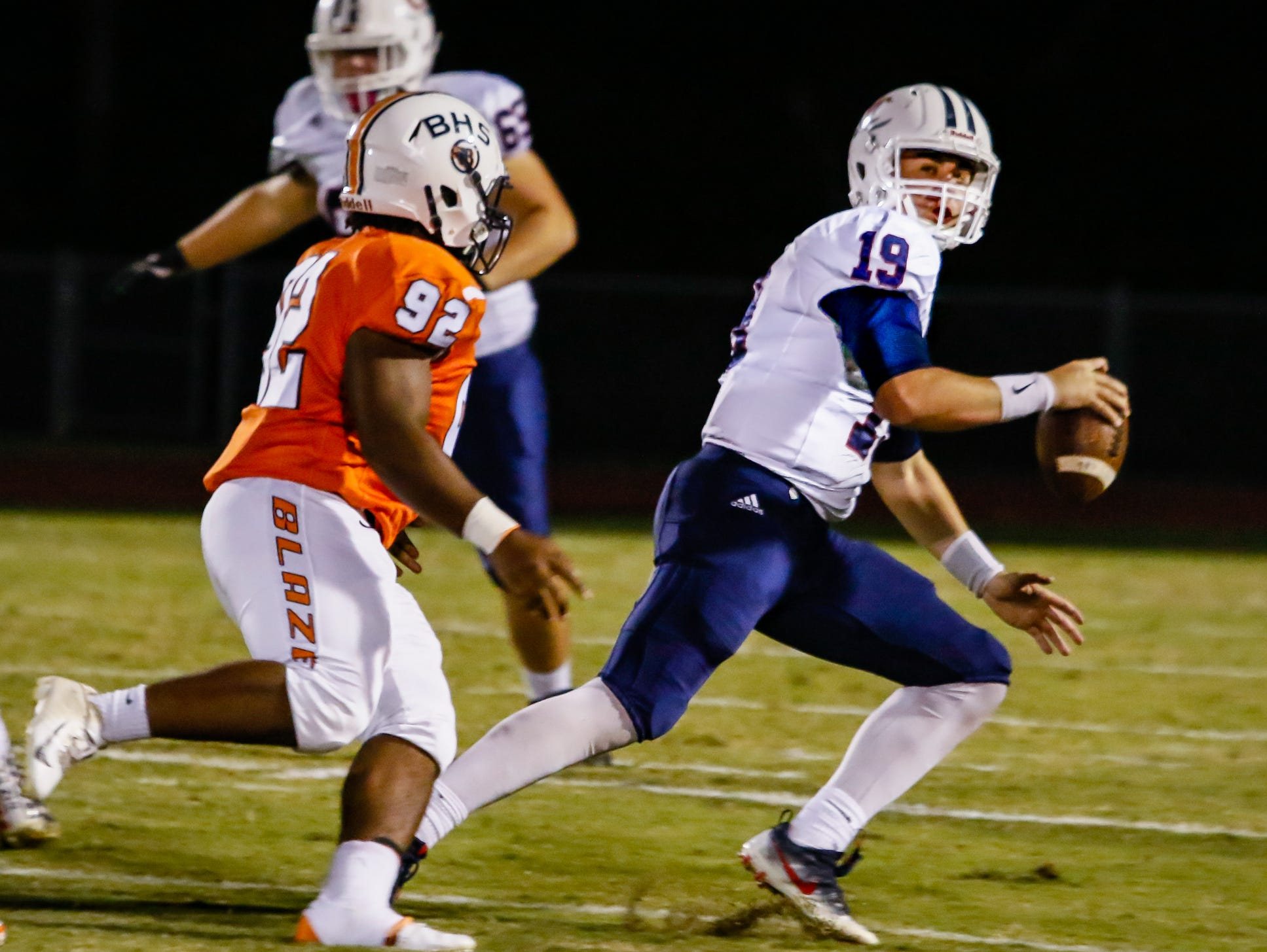 Cookeville quarterback Robert Espinosa tries but ultimately fails to escape being tackled by Blackman's Lorenzo Smith.
