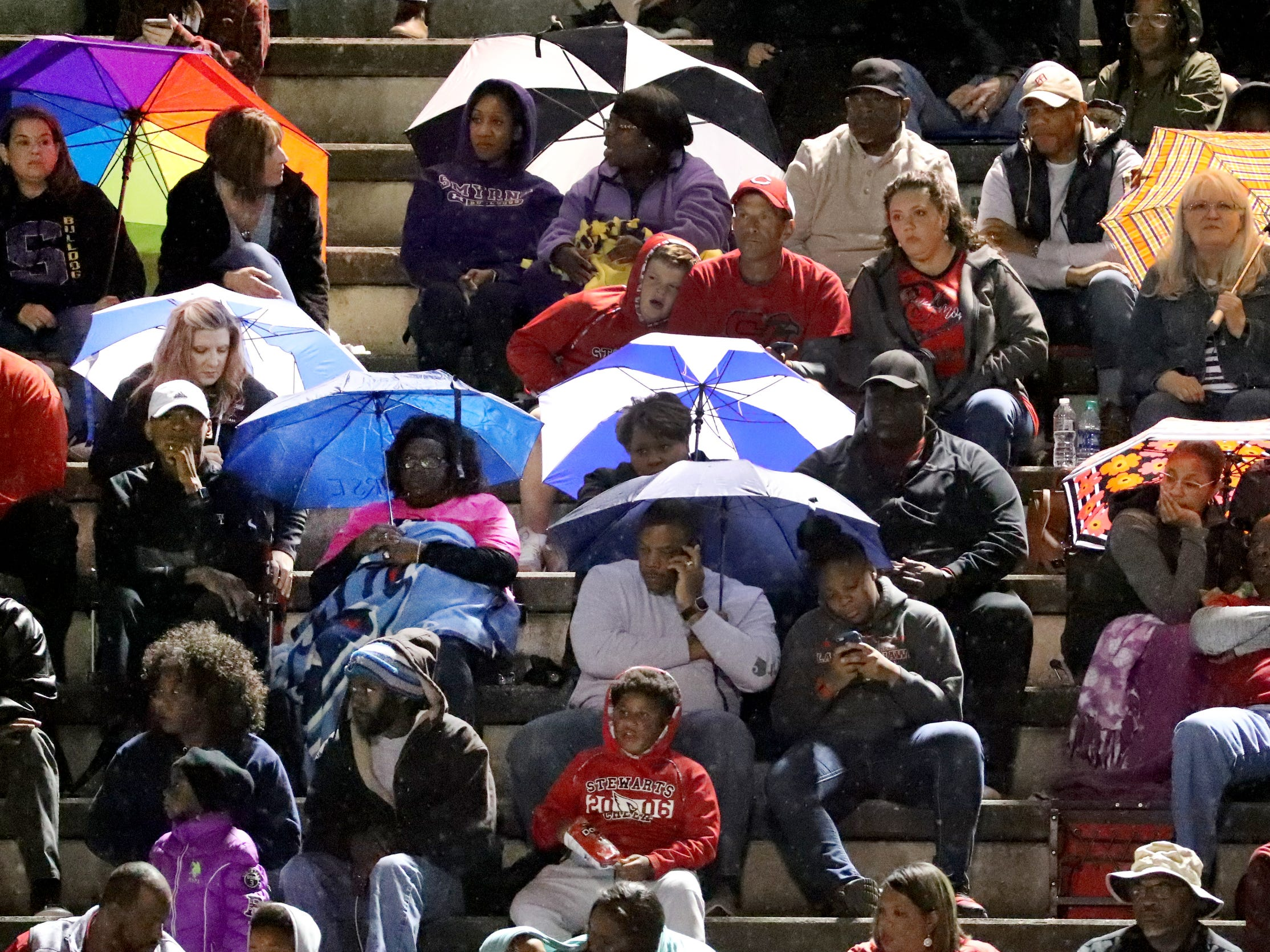 Smyrna fans try to stay dry as rain sprinkles down during the game against Stewarts Creek at Smyrna High School on Friday, Oct. 12, 2018.