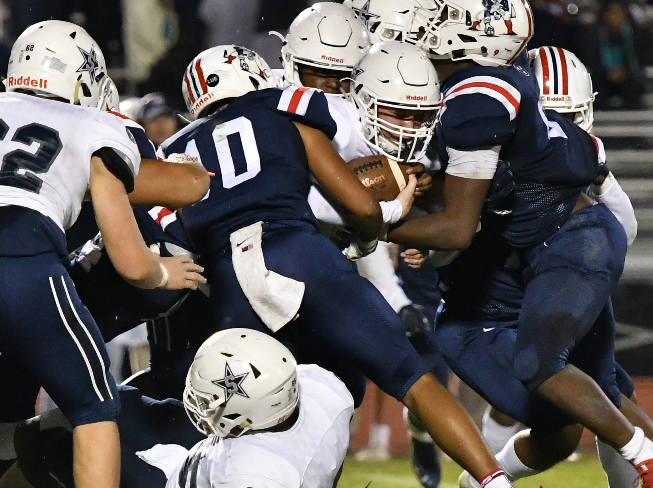The Oakland defense swarms a Siegel running back Friday night.