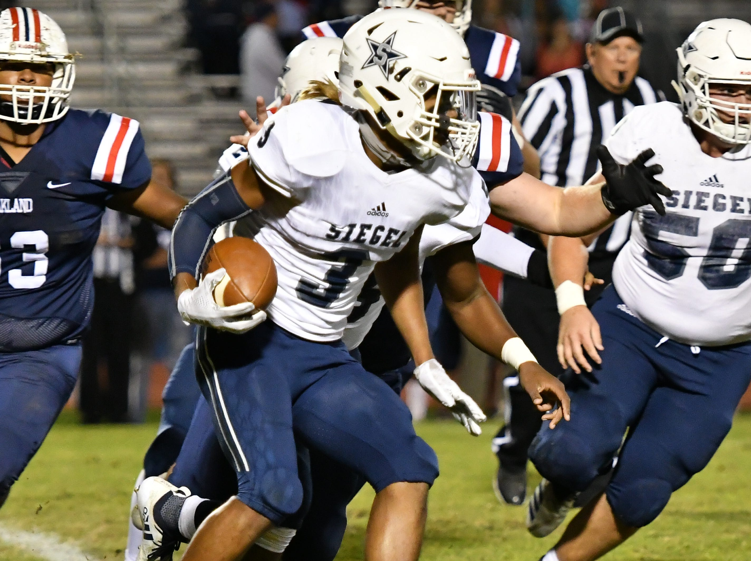 Siegel's Joseph Perry rushes for yardage against Siegel Friday night.