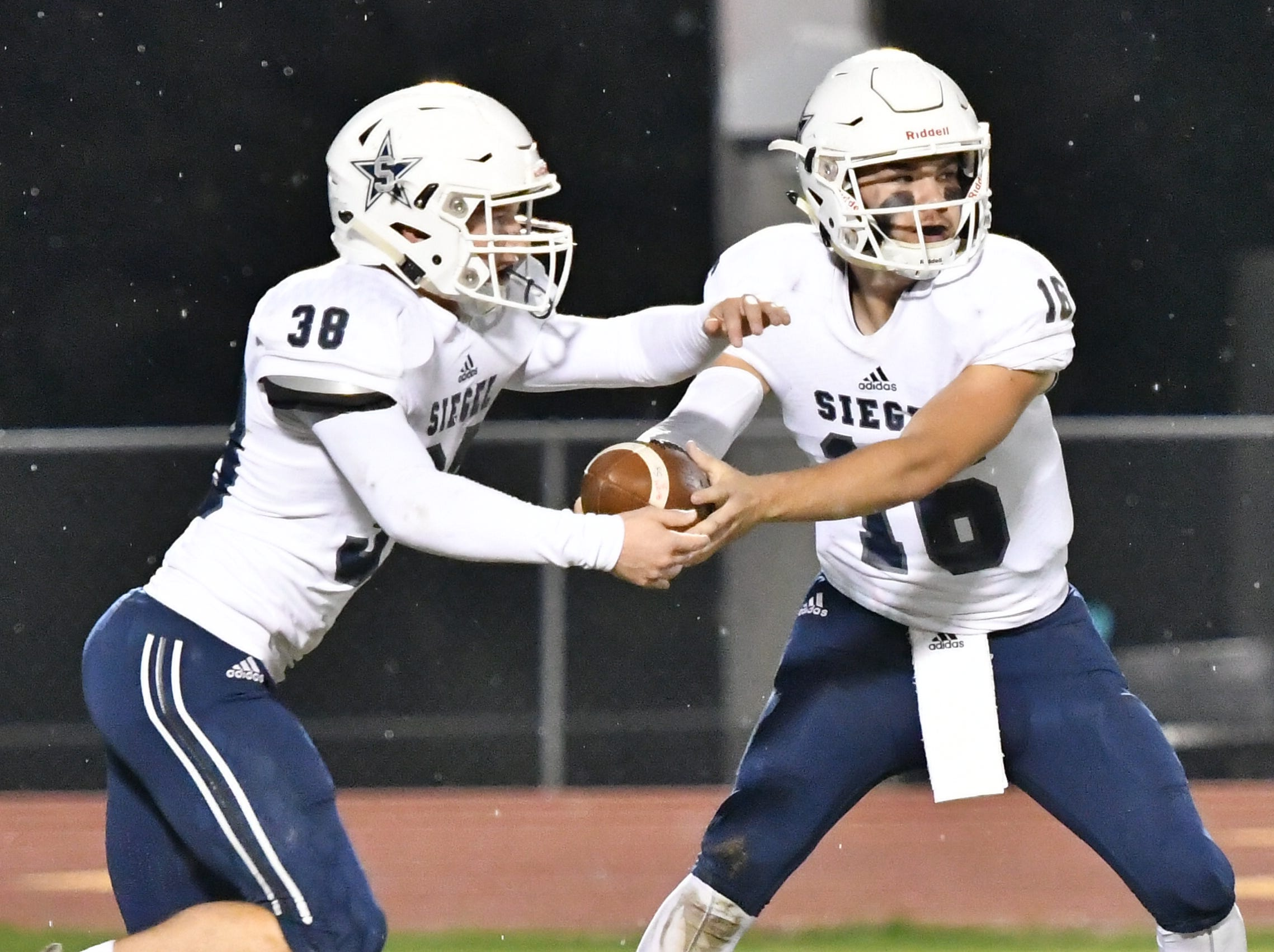 Siegel QB Tucker Sears hands off to Brandon Ricks Friday night against Oakland.