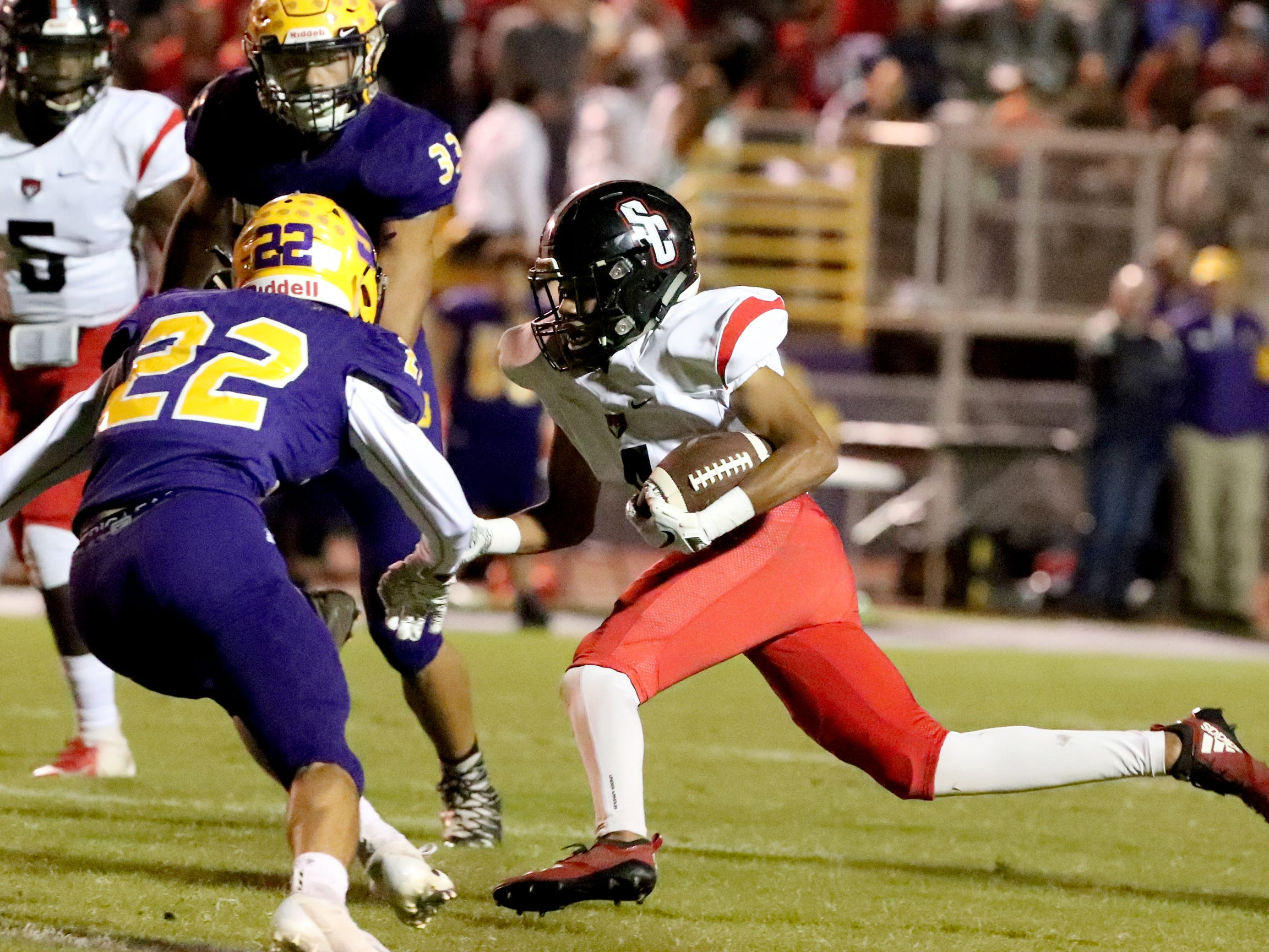 Stewarts Creek's Keo Polk (4) runs the ball as Smyrna's Emerson Combs (22) moves in for a tackle at Smyrna High School on Friday, Oct. 12, 2018.