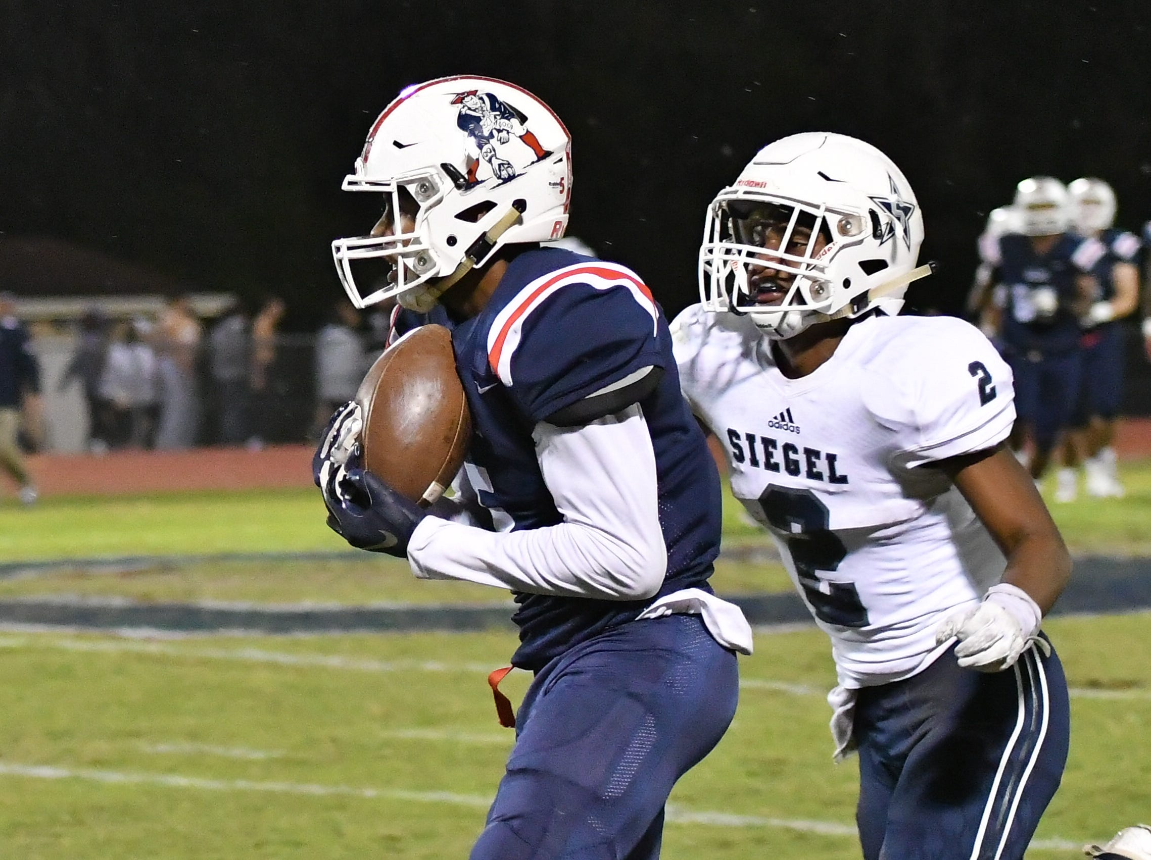 Oakland's Woodi Washington makes a reception Friday night as Siegel's Ryan Wilson moves in.