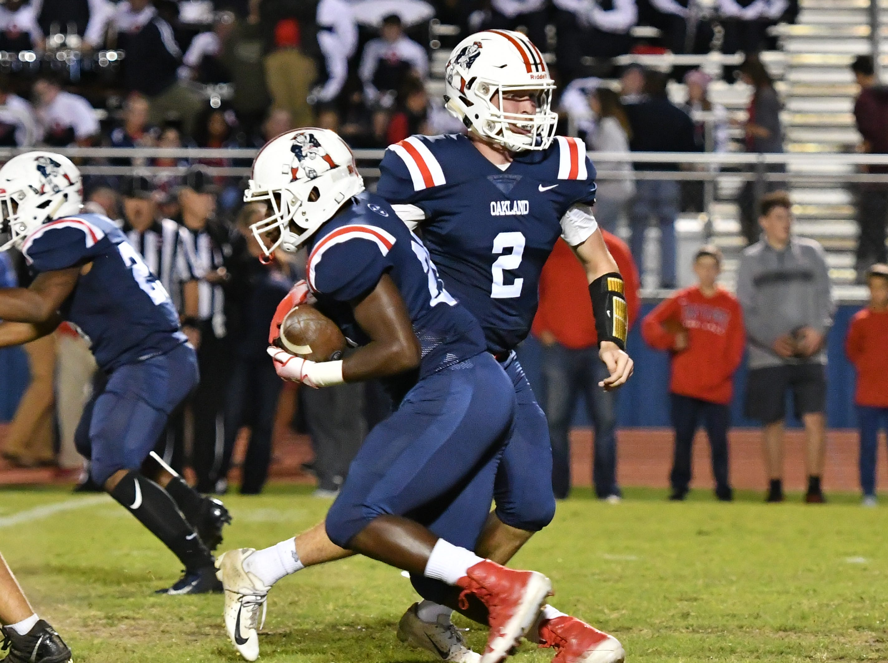 Oakland QB Brevin Linnell hands off to Xavier Myers Friday night against Siegel.