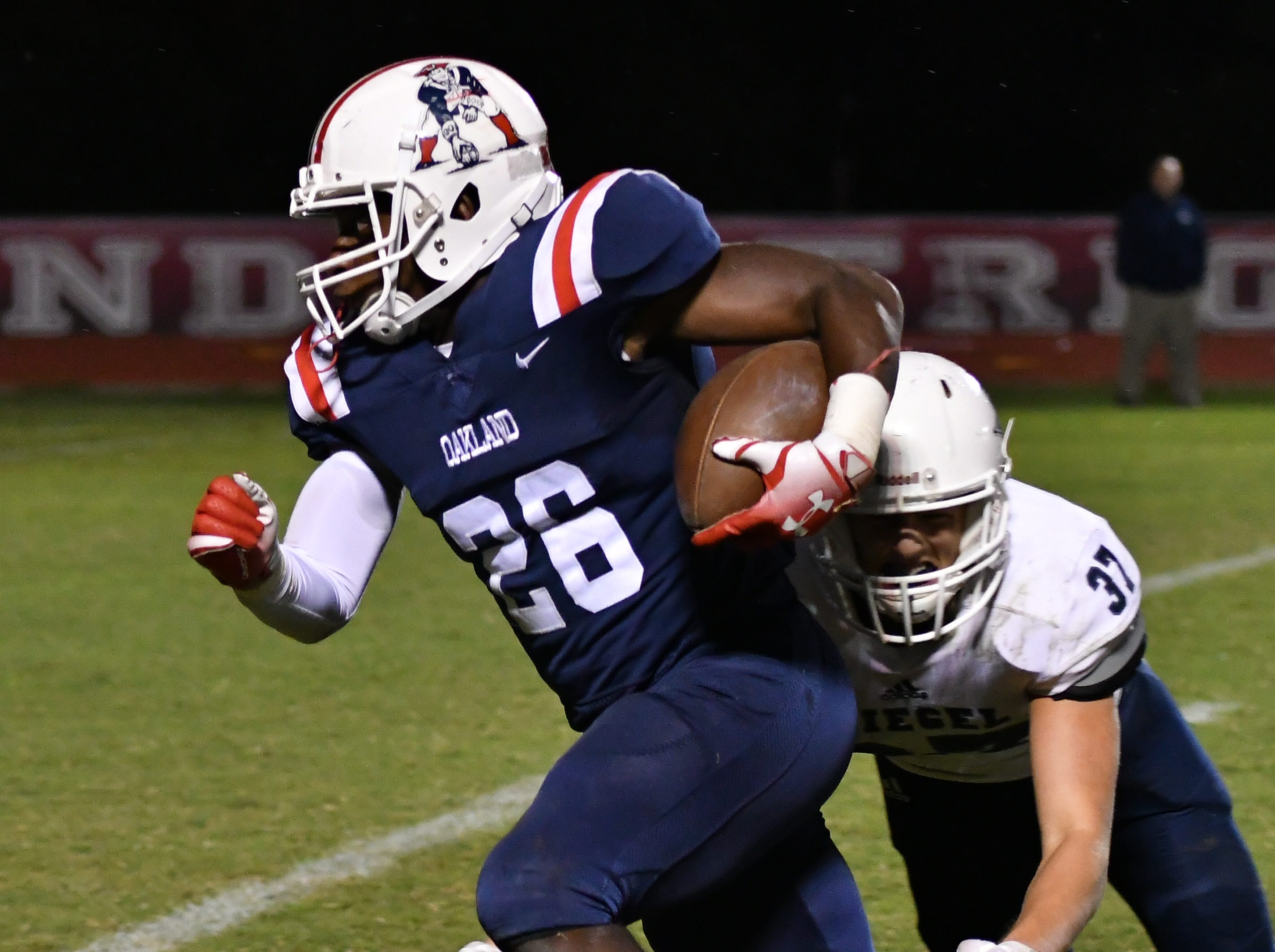 Oakland's Xavier Myers heads downfield as Siegel's Patrick Moss tries for the tackle.