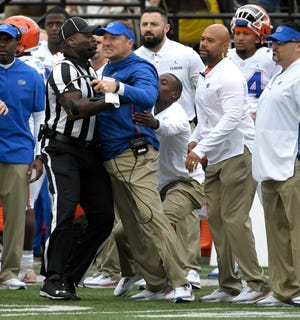 An official holds back Florida head coach Dan Mullen during a game at Vanderbilt Stadium in Nashville on Saturday, Oct. 13, 2018.