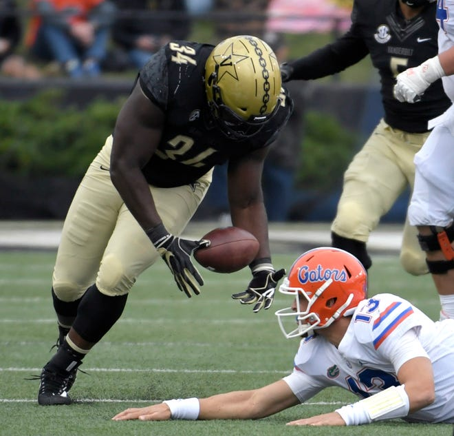 Vanderbilt Commodores defensive lineman Dare Odeyingbo (34) tries to recover a fumble from Florida Gators quarterback Feleipe Franks (13) during a game at Vanderbilt Stadium in Nashville on Saturday, Oct. 13, 2018.