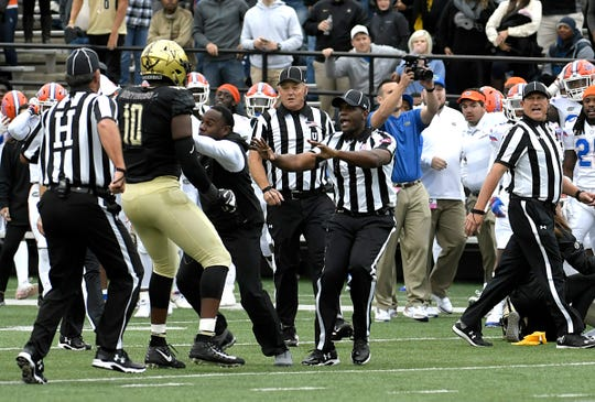 Vanderbilt head coach Derek Mason, center, holds his players back from the Florida sidelines during a game at Vanderbilt Stadium in Nashville on Saturday, Oct. 13, 2018.