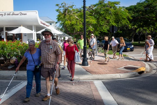 Colleen Martin and her husband Randy Marty cross the street during the White Can Walk held by the Lighthouse of Collier foundation on Saturday morning.