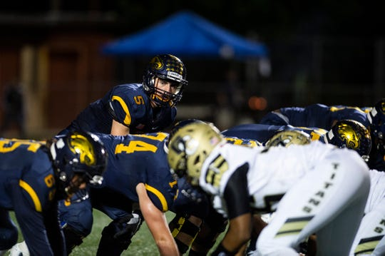 Naples High School's  Drew Wiltsie calls a play before the snap during a game against Golden Gate High School in Naples, Fla., on Friday, October 12, 2018.
