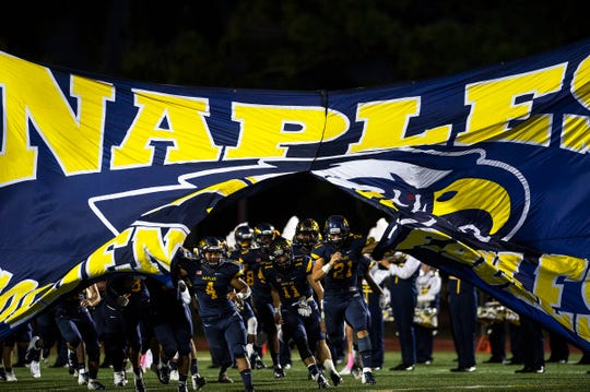 Naples High School's football team takes the field during a game against Golden Gate High School in Naples, Fla., on Friday, October 12, 2018.