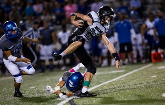 Colby Singletary of Palmetto Ridge High School almost gets tackled during the game on Friday, October 12, 2018, at Barron Collier High School in Naples.