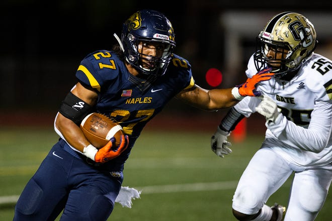 Naples High School's Chez Mellusi makes his way around a defender during a game against Golden Gate High School on Friday at Staver Field. The Golden Eagles rallied in the second half for a 31-10 victory.