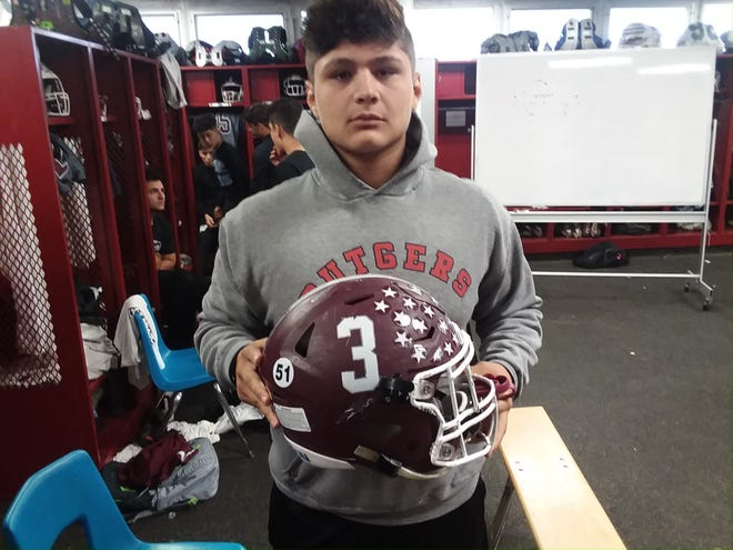 Wayne Hills team captain Anthony Puntolillo holding his helmet, with Lou Brandt's number 51 on the back.