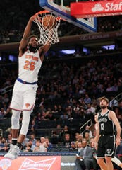 New York Knicks' Mitchell Robinson (26) dunks in front of Brooklyn Nets' Joe Harris (12) during the first half of an NBA preseason basketball game Friday, Oct. 12, 2018, in New York.