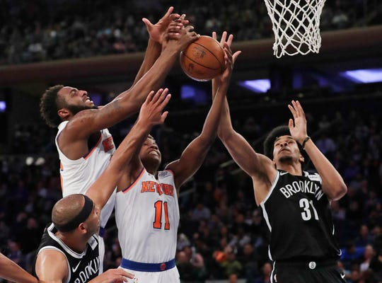New York Knicks' Mitchell Robinson, left, and Frank Ntilikina, center, and Brooklyn Nets' Jarrett Allen (31) reach for a rebound during the first half of a preseason NBA basketball game Friday, Oct. 12, 2018, in New York.