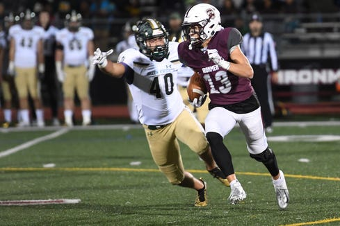 St. Joseph at Don Bosco on Friday, October 12, 2018. DB #13 Christian Dremel avoids a tackle by SJ #40 Justin Malvasia in the second quarter.