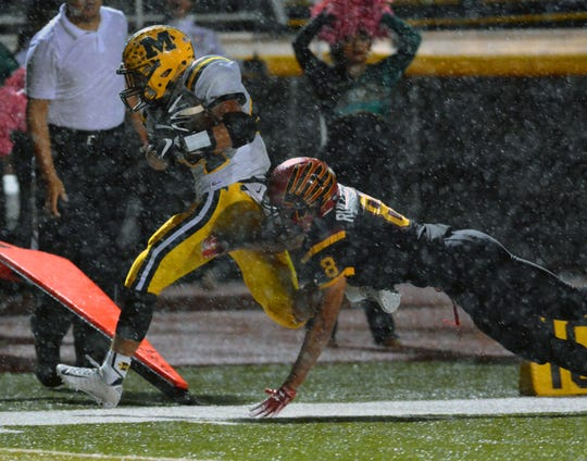 Mayfield's A.J. Parra catches a pass and gains enough for a first down against Centennial High's Karsten Rueckner in the rain on Friday night at the Field of Dreams.