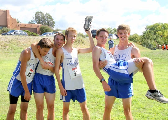 The Carlsbad Cavemen varsity team of Kevin Calbani, Coltan Lee, Dane Johnson, Cody Dew and Caleb Herdon celebrate finishing Saturday's race in Roswell. The Cavemen took home second place as a team with all five runners finishing in the top-25.