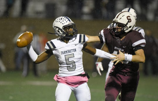 Farmington quarterback Anthony Reaves (5) is chased down by Seaholm defensive end Paul Jokisch (45).