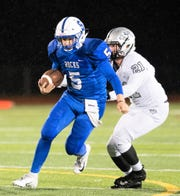 Salem quarterback Tyler Overaitis (5) is chased by Plymouth tackler Jackson Rogers.