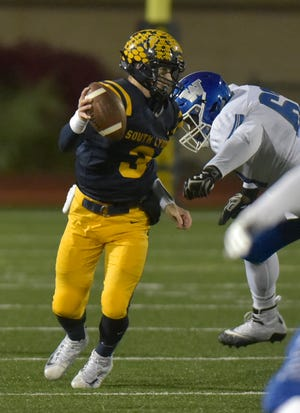South Lyon quarterback Connor Fracassi (3) evades Walled Lake Western's Justin Collier (63) in last week's Lakes Valley Conference clash.