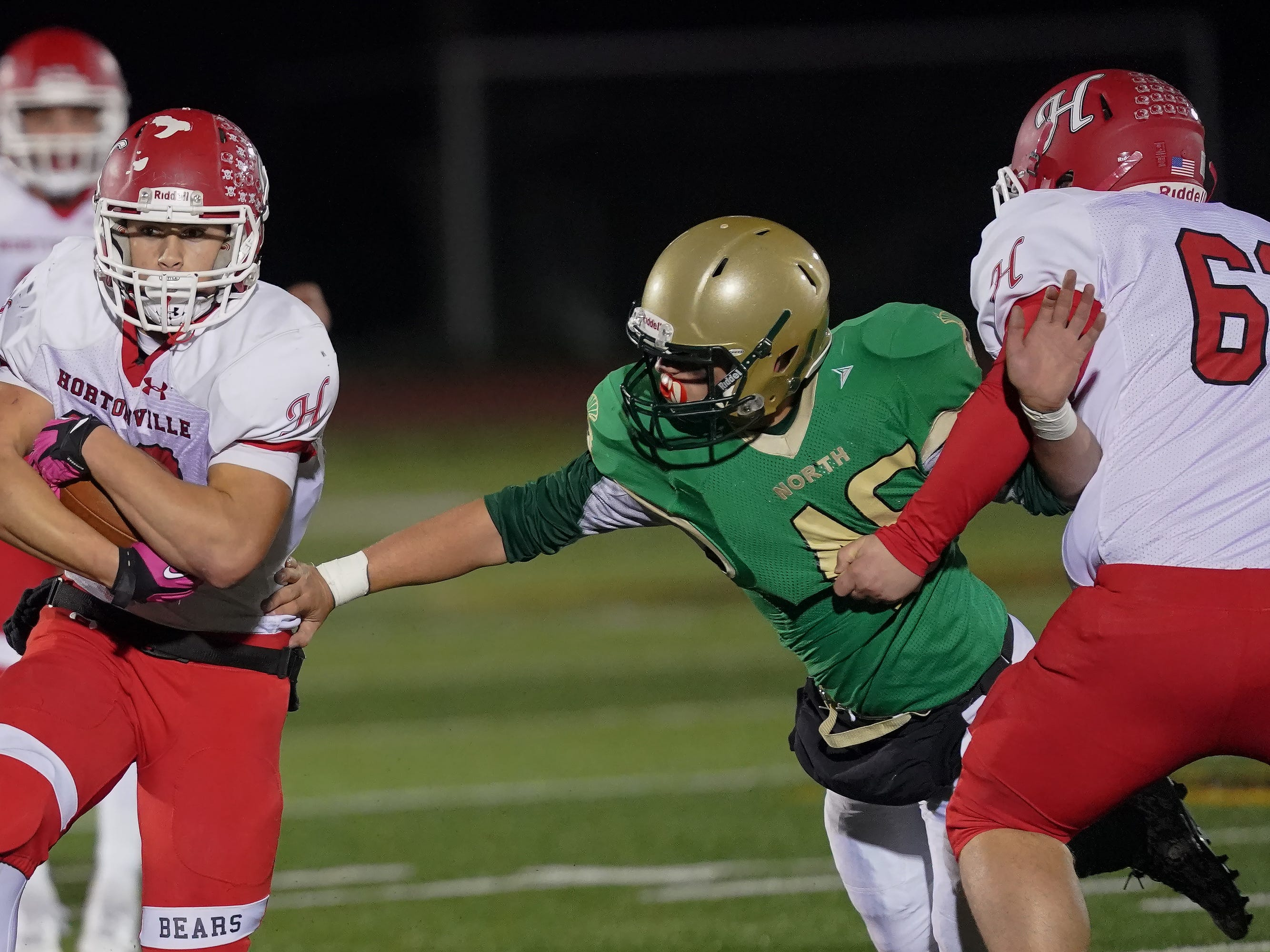 Jose Concepcion (22) of Hortonville uses both hands to protect the ball as he runs up the middle. The Oshkosh North Spartans hosted the Hortonville Polar Bears in an FVA-South conference matchup Friday evening, October 12, 2018 at J. J. Keller Field at Titan Stadium.