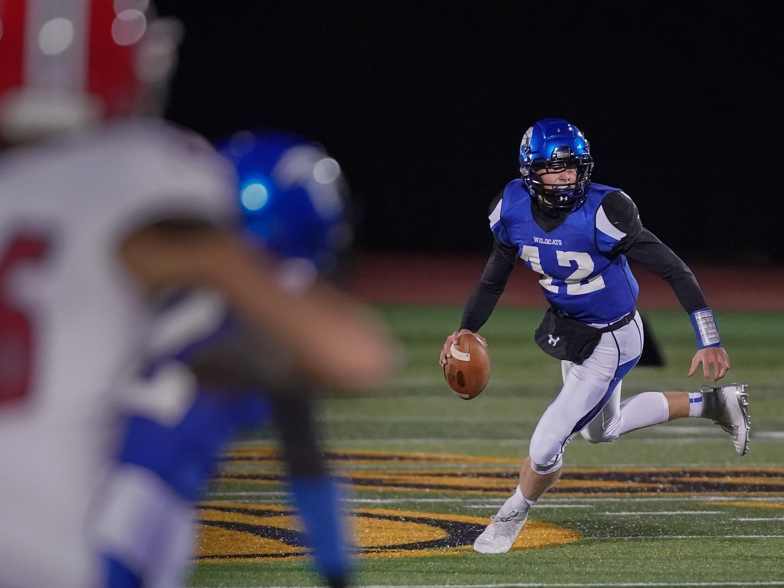 Oshkosh West quarterback Jake Ketter (12) rolls out to pass. The Oshkosh West Wildcats hosted the Neenah Rockets in an FVA-South conference matchup Friday evening, October 12, 2018 at J. J. Keller Field at Titan Stadium.