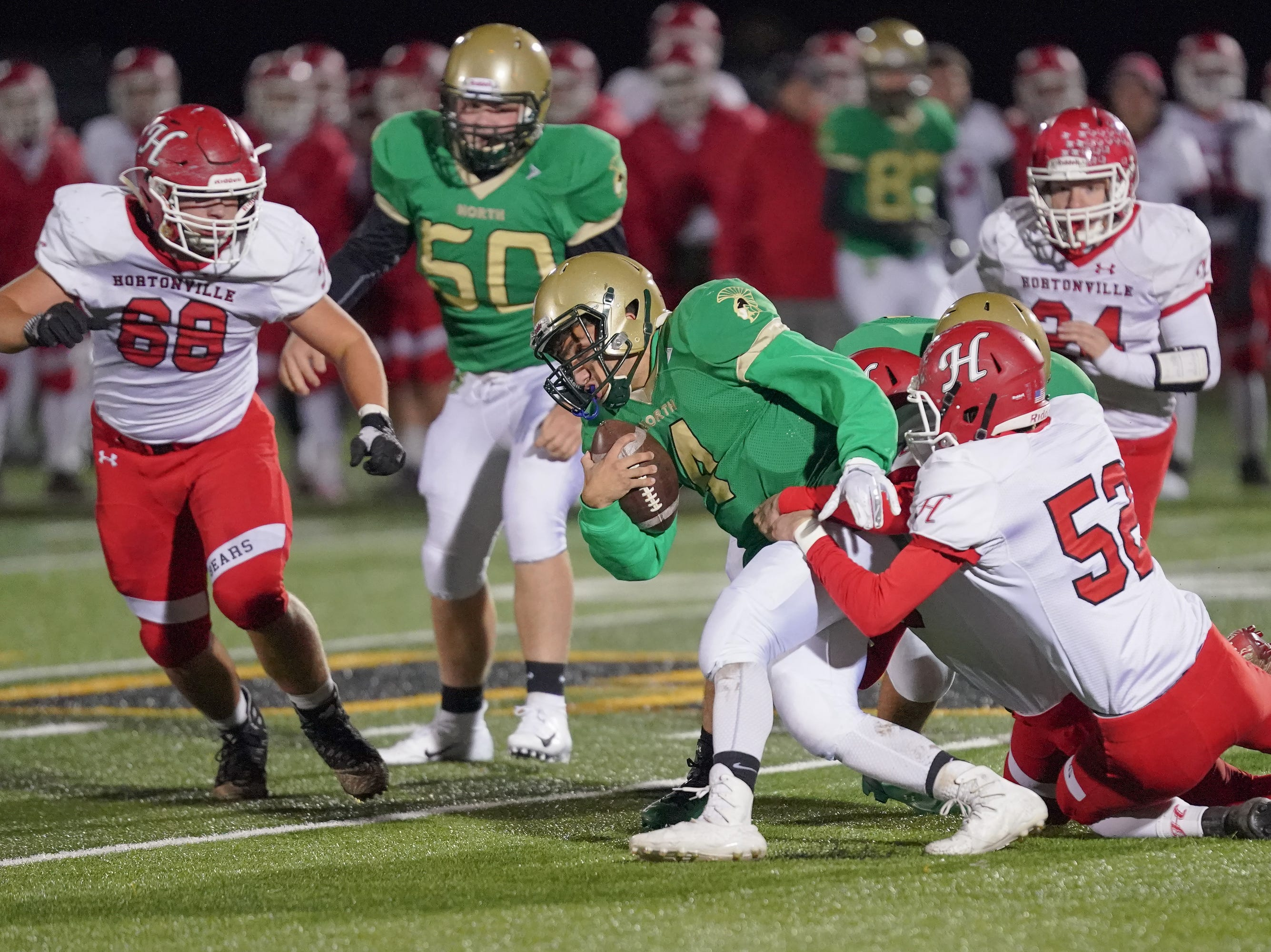 Oshkosh North quarterback Alex Garland (4) struggles for a gain in the fourth quarter. The Oshkosh North Spartans hosted the Hortonville Polar Bears in an FVA-South conference matchup Friday evening, October 12, 2018 at J. J. Keller Field at Titan Stadium.