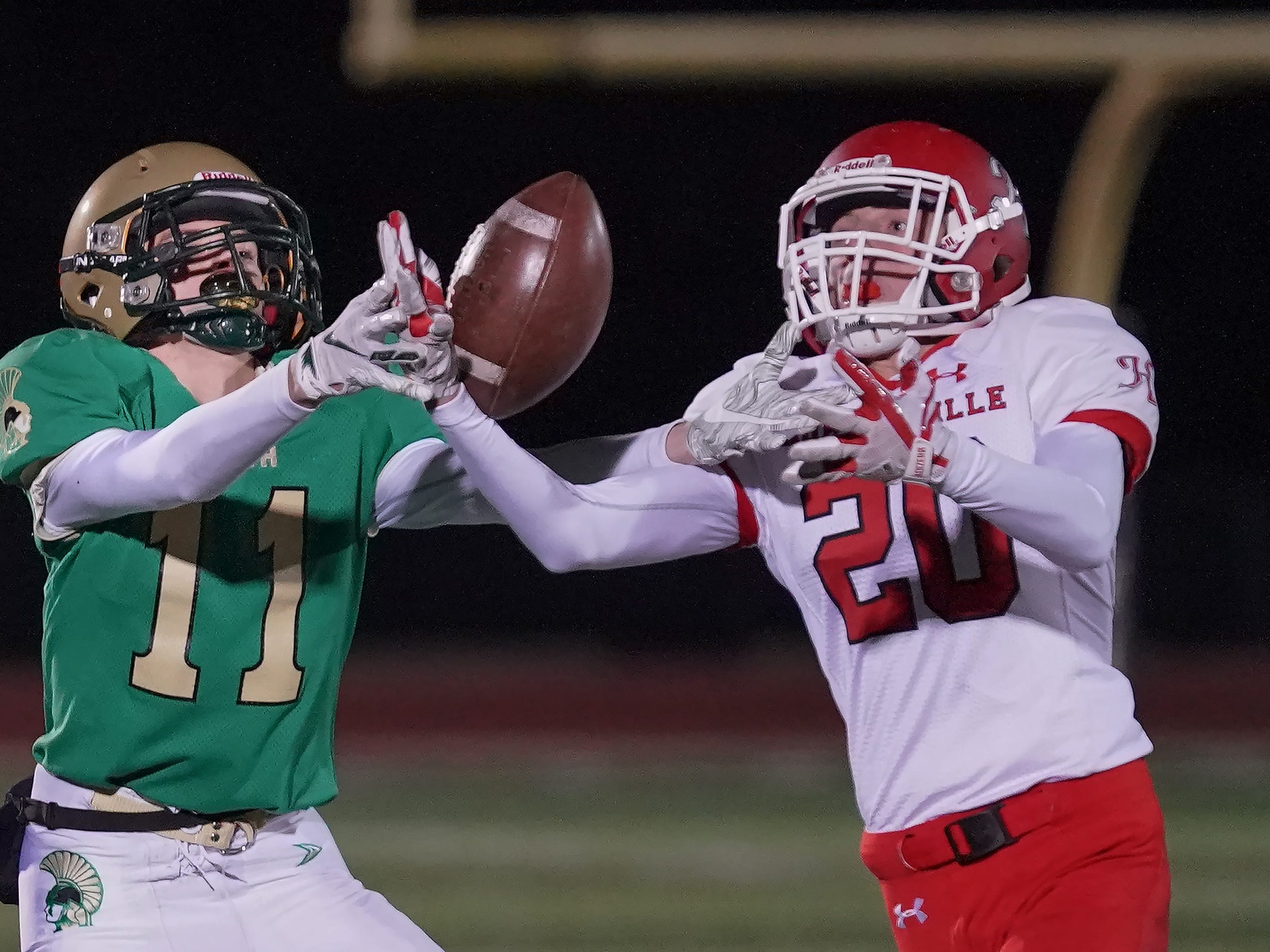 Trevor Van Dyke (11) of Oshkosh North and Logan Grossman (20) of Hortonville battle over a pass. The Oshkosh North Spartans hosted the Hortonville Polar Bears in an FVA-South conference matchup Friday evening, October 12, 2018 at J. J. Keller Field at Titan Stadium.
