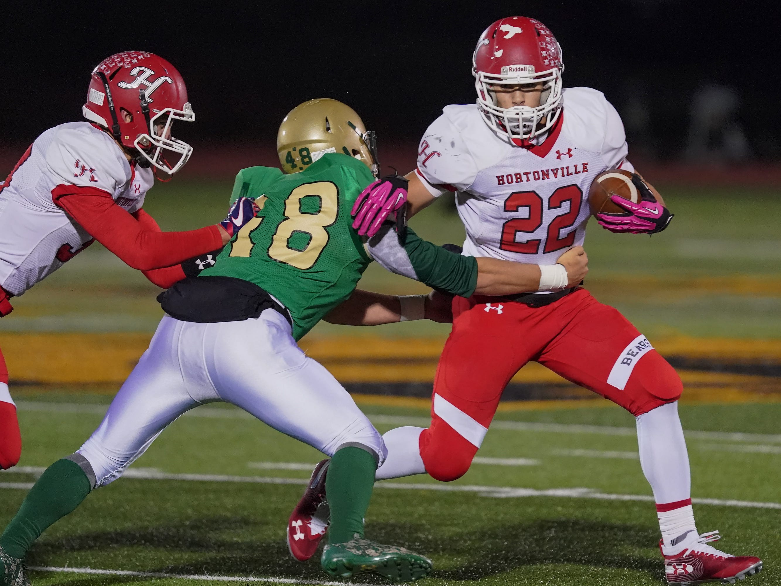 Logan Boese (48) of Oshkosh North tries to bring down Jose Concepcion (22) of Hortonville. The Oshkosh North Spartans hosted the Hortonville Polar Bears in an FVA-South conference matchup Friday evening, October 12, 2018 at J. J. Keller Field at Titan Stadium.
