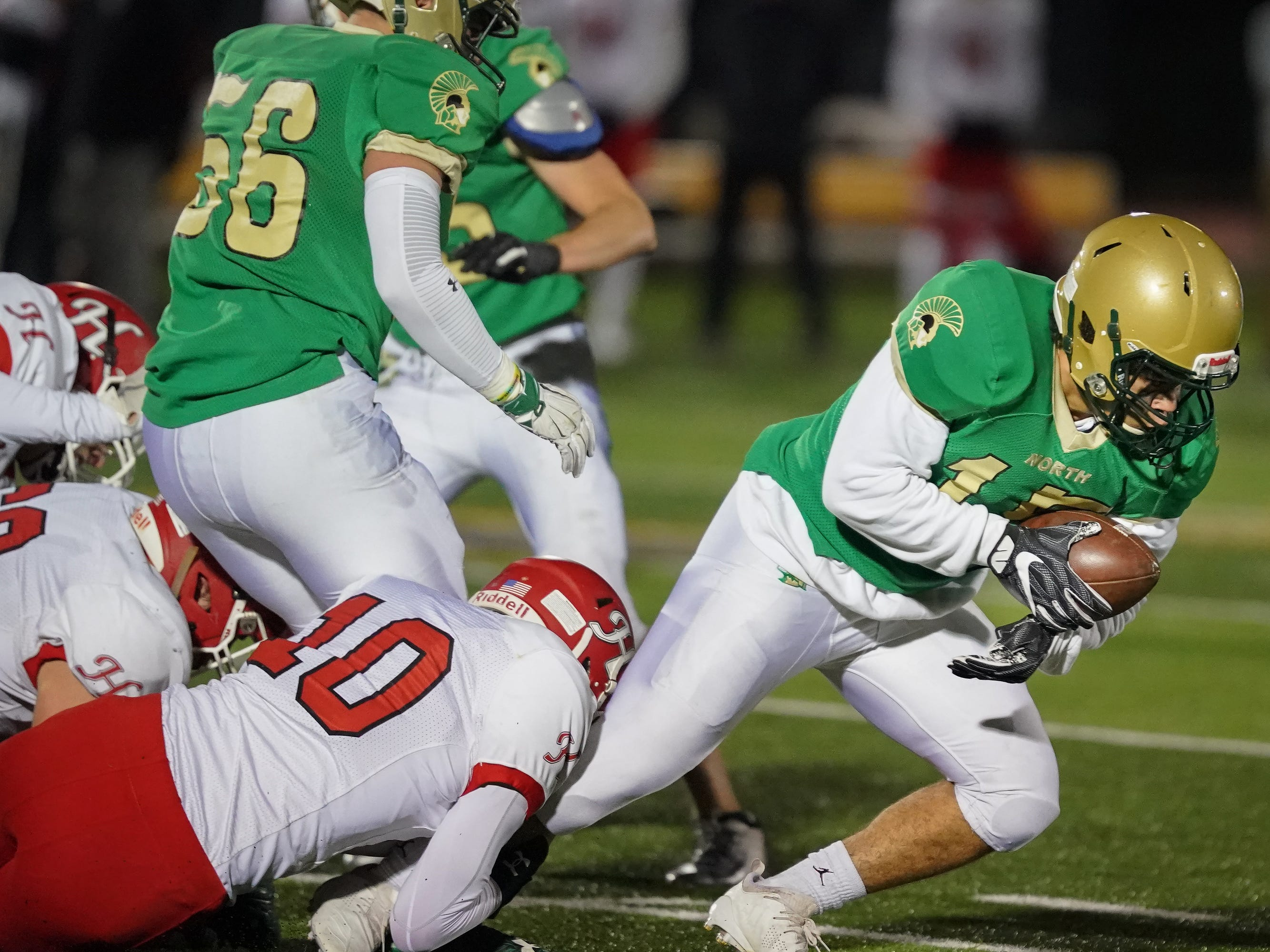 Dion Stulo (15) gets pulled down after a short gain. The Oshkosh North Spartans hosted the Hortonville Polar Bears in an FVA-South conference matchup Friday evening, October 12, 2018 at J. J. Keller Field at Titan Stadium.