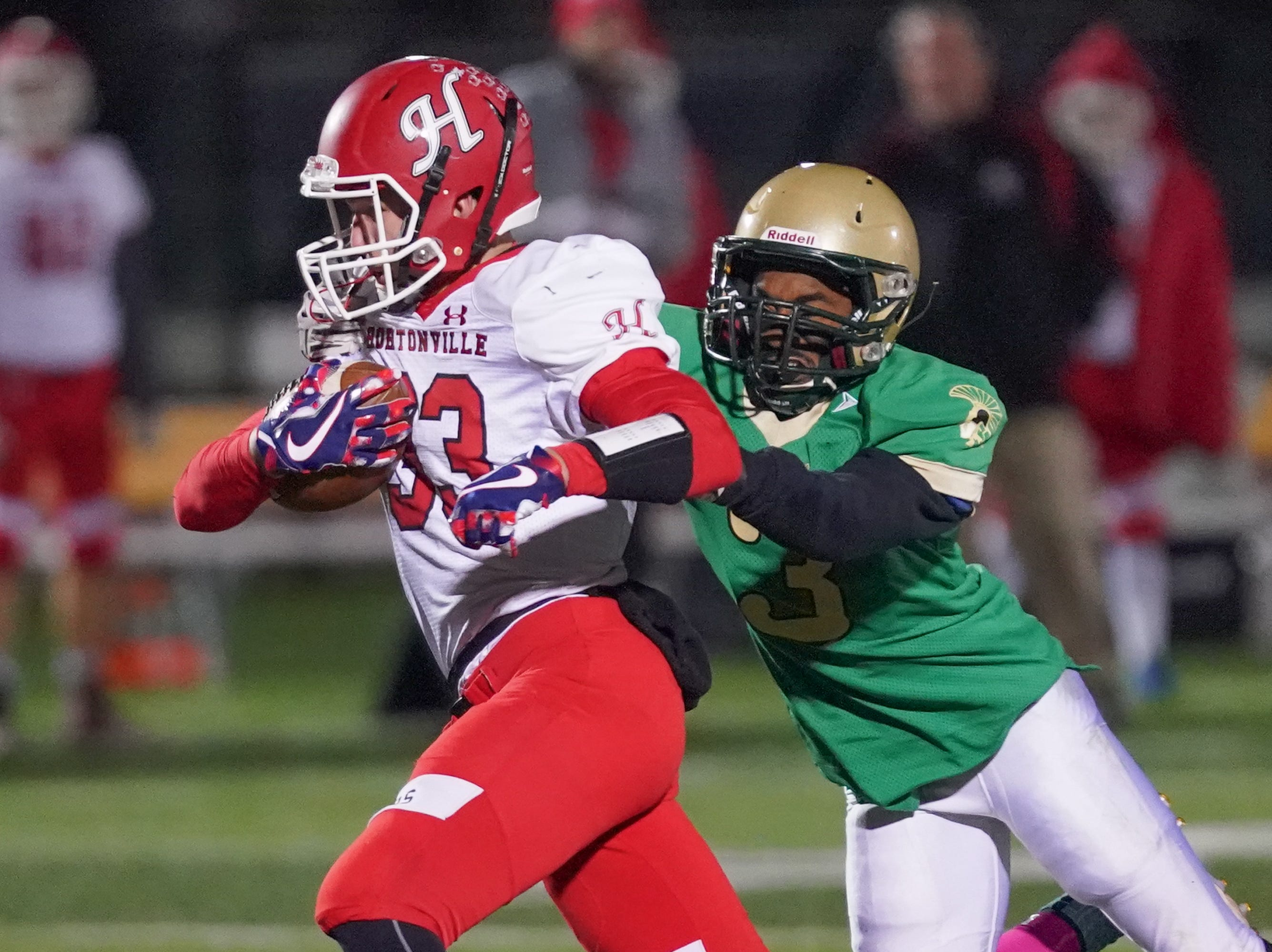 Dylan Schmidt (33) of Hortonville tries to outrun the grasp of Travon Lee (3) of Oshkosh North. The Oshkosh North Spartans hosted the Hortonville Polar Bears in an FVA-South conference matchup Friday evening, October 12, 2018 at J. J. Keller Field at Titan Stadium.