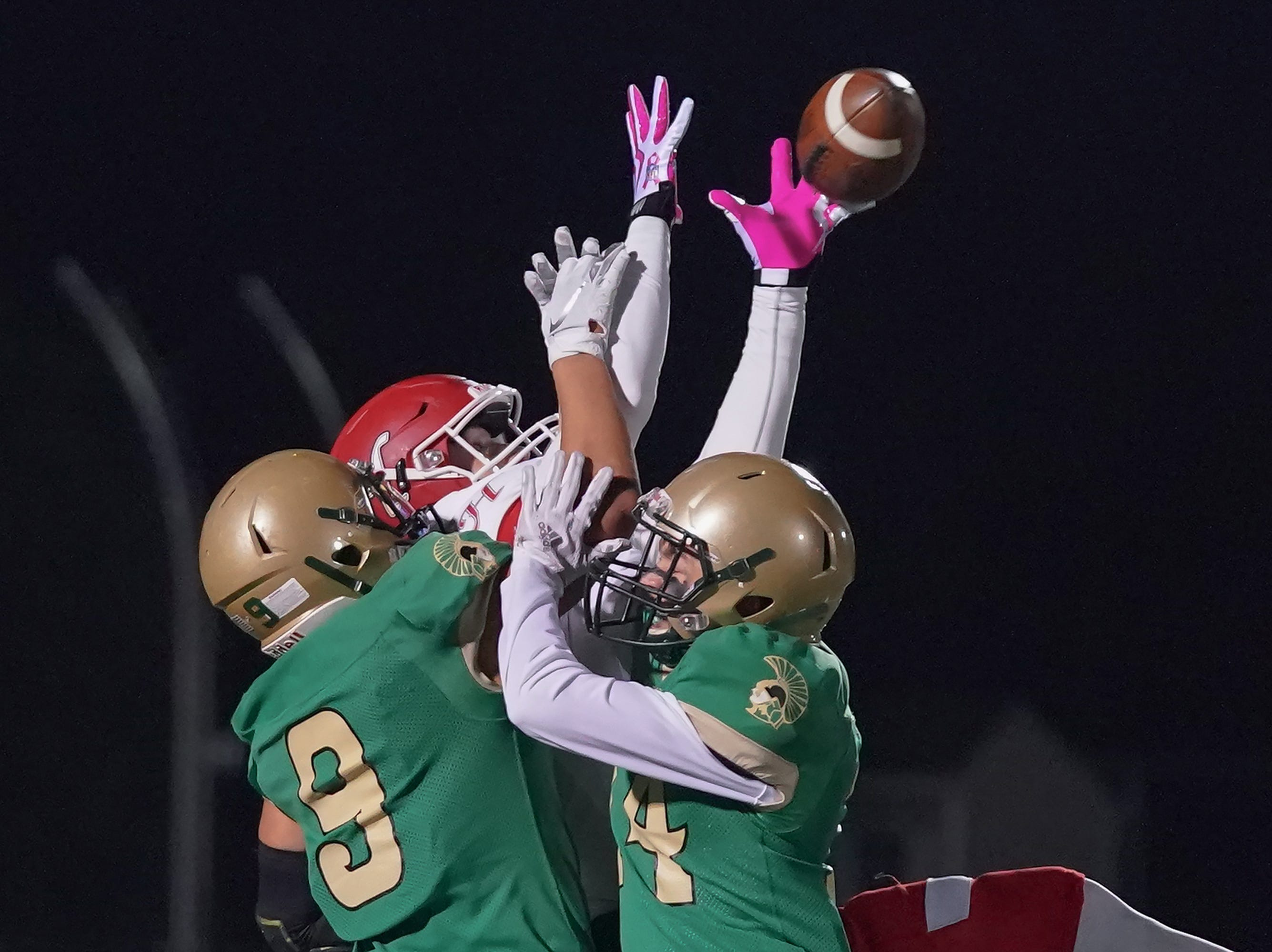 Josh Giese (84) of Hortonville can't make a catch while covered by Aittipon Thao (9) and Caden McCartney (14) of Oshkosh North. The Oshkosh North Spartans hosted the Hortonville Polar Bears in an FVA-South conference matchup Friday evening, October 12, 2018 at J. J. Keller Field at Titan Stadium.