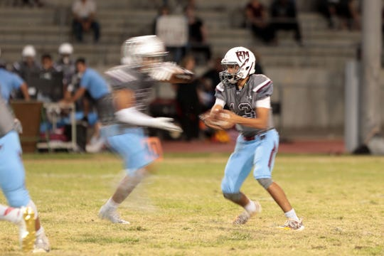 Rancho Mirage quarterback Cesar Vela hands off the ball against Palm Springs on Friday, October 12, 2018 in Palm Springs.
