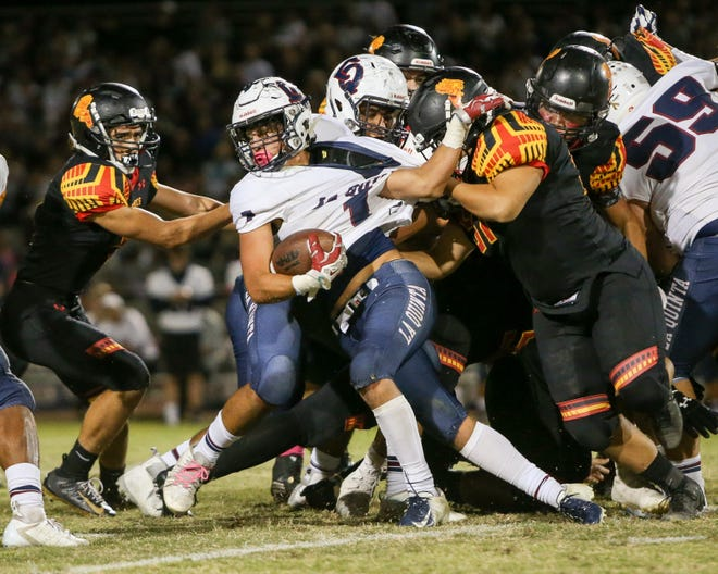 La Quinta's Marcus McAvoy tries to pull away from a Palm Desert defender during the epic Flag Game that went the way of the Aztecs 34-32.