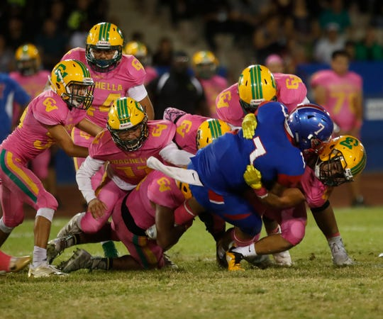 A swarm of pink-clad Coachella Valley Arabs tackled Indio's Aubuchon Martinez during Friday night's game won by Coachella Valley 61-38