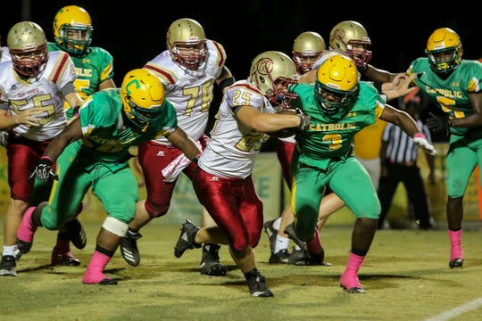 Northview's Trent Peebles (25) bursts through the Crusaders' defensive line in the homecoming game at Catholic High School on Friday, October 12, 2018.
