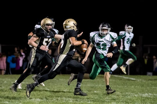 Delone Catholic's Evan Brady scrambles out of the pocket during play against Fairfield on Friday, October 12, 2018. The Squires won 57-3.