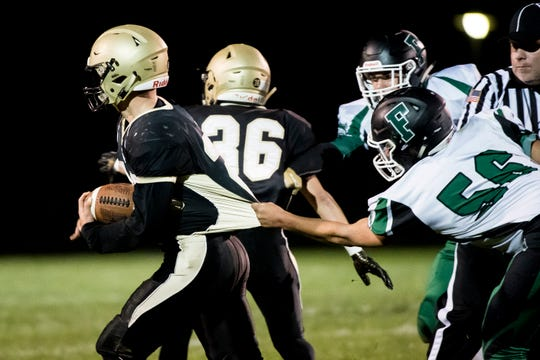 Delone Catholic's Tyler Monto escapes the grasp of Fairfield's Zach Rutherford while carrying the ball on Friday, October 12, 2018. The Squires won 57-3.