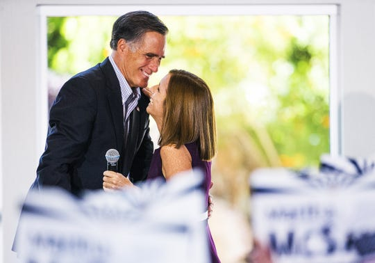 Former Massachusetts Gov. Mitt Romney hugs Martha McSally during a rally at the Falls Event Center in Gilbert, October 12, 2018.