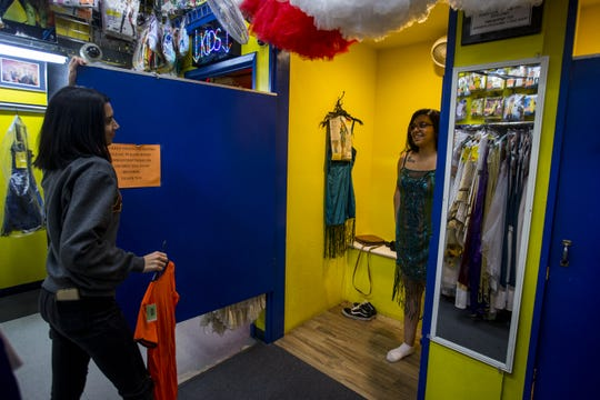 April Carrillo watches as Cynthia Nieto tries on a costume at Easley's Fun Shop on Thursday, Oct. 11, 2018, in Phoenix. The costume and gag store is closing at the end of the year after operating for 72 years.