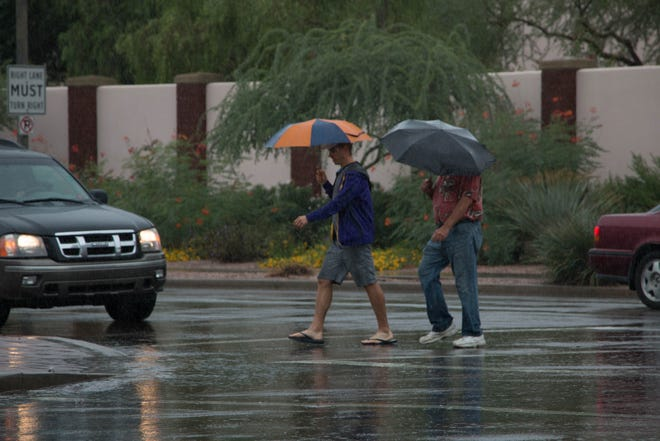 Pedestrians in Phoenix faced wind and rain caused by the remnants of Hurricane Sergio.