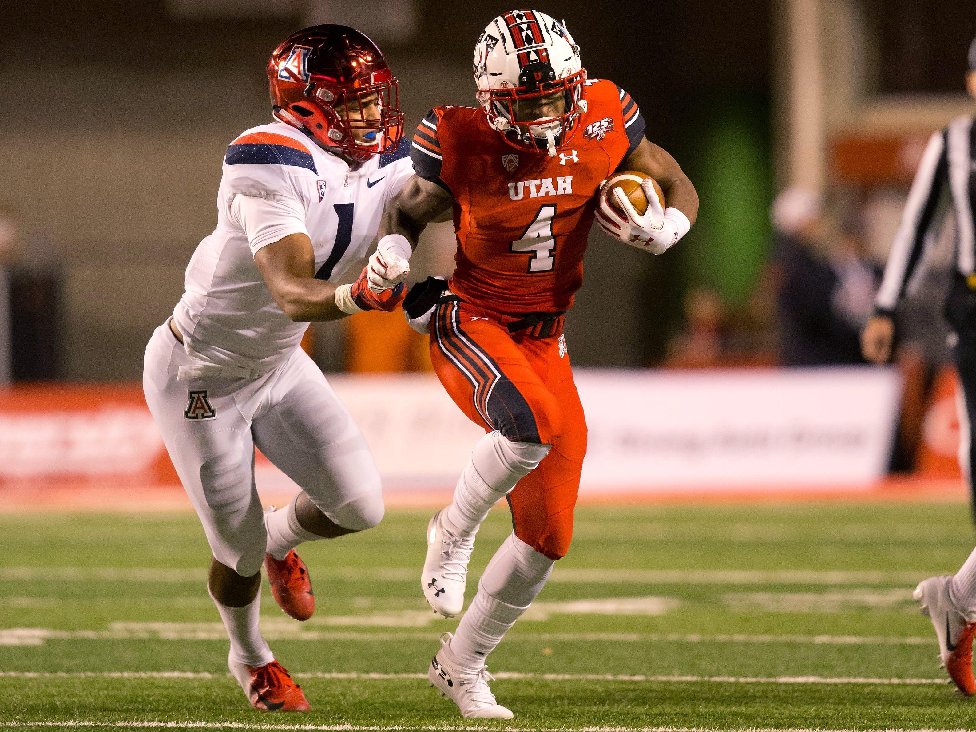 Oct 12, 2018; Salt Lake City, UT, USA; Utah Utes running back TJ Green (4) runs with the ball as Arizona Wildcats linebacker Tony Fields II (1) pursues the play during the first half at Rice-Eccles Stadium.