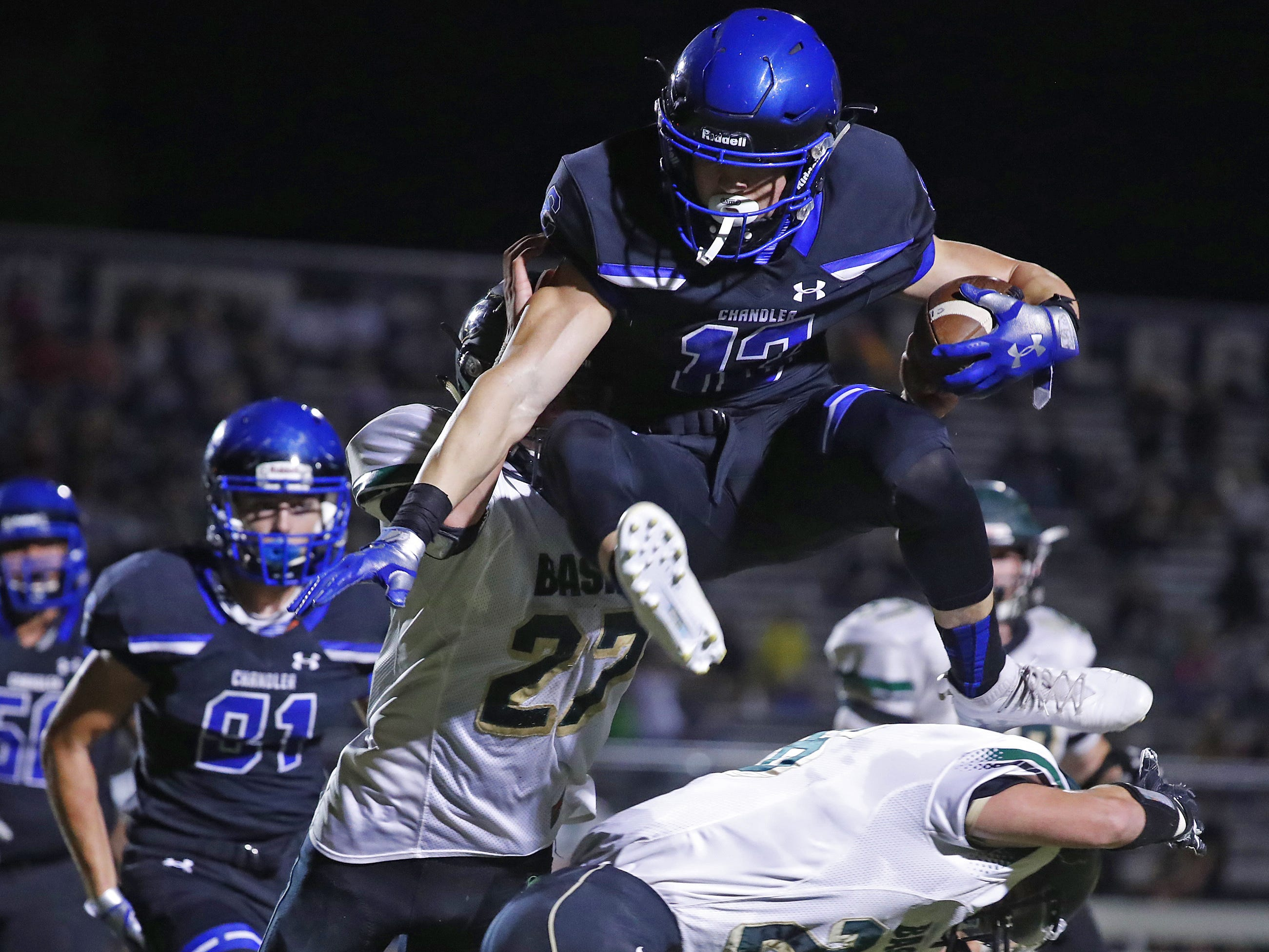 Chandler's Gunner Maldanado (13) hurdles a tackle from Basha's Dylan Quinn (25) at Chandler High School in Chandler, Ariz. on October 12, 2018. #azhsfb