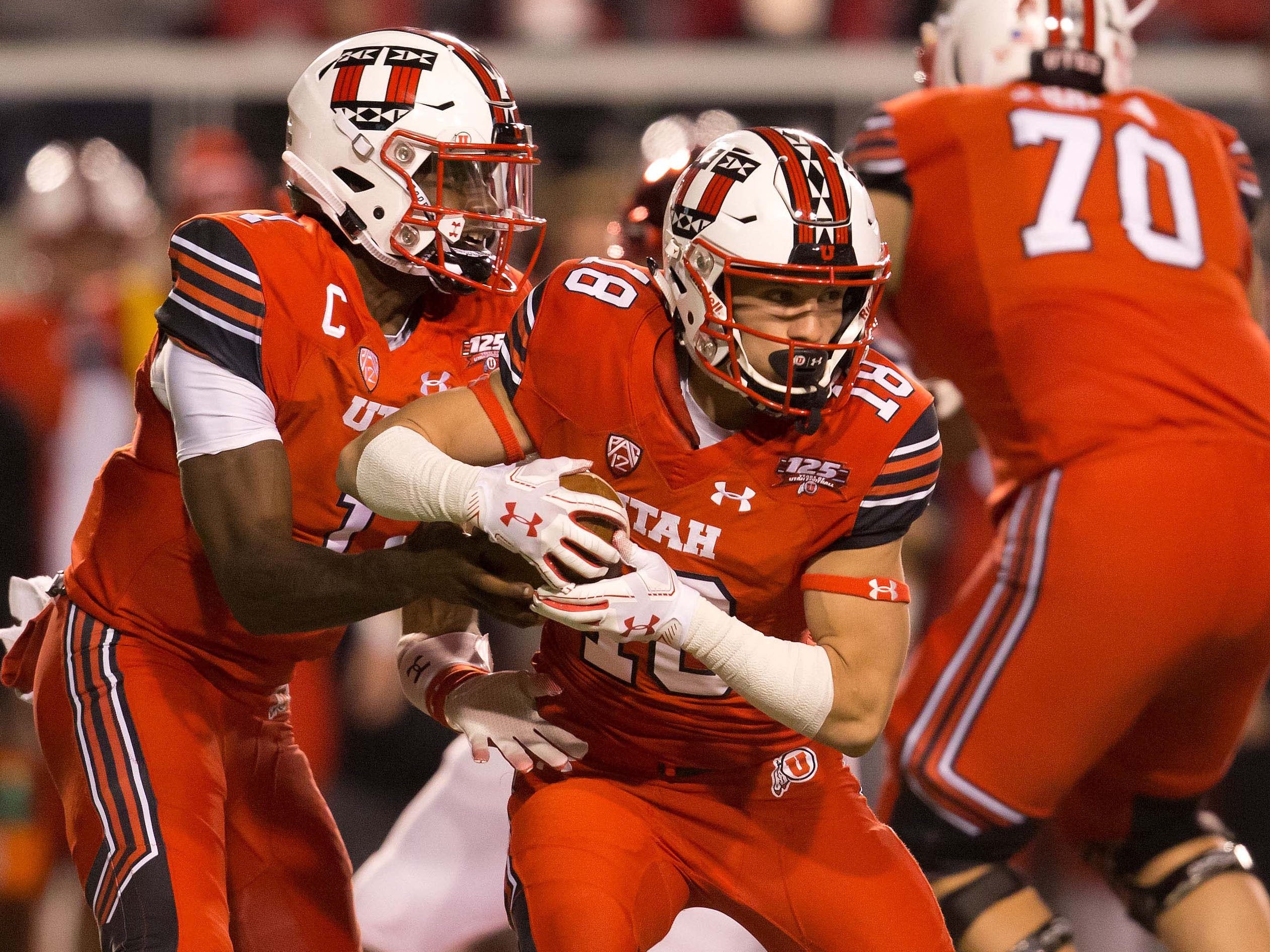 Oct 12, 2018; Salt Lake City, UT, USA; Utah Utes quarterback Tyler Huntley (1) hands off to wide receiver Britain Covey (18) during the first quarter against the Arizona Wildcats at Rice-Eccles Stadium.